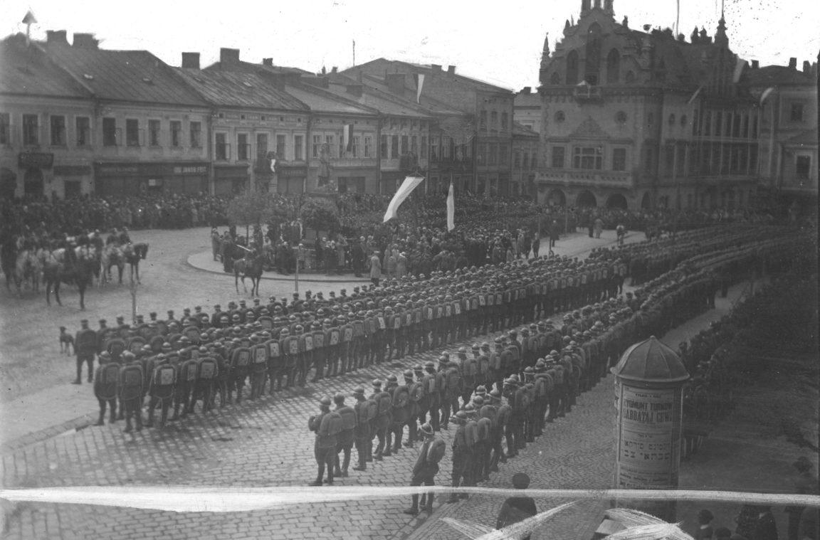 Widok ogólny Rynku w Rzeszowie podczas uroczystości. Widoczne m.in. pomnik Tadeusza Kościuszki, ratusz. W wielu miejscach widoczne flagi. Na rynku stoją w szyku oddziały wojska, rok 1930-05-03
